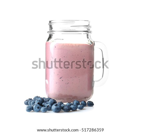 Mason jar with tasty smoothie and blueberries on light background