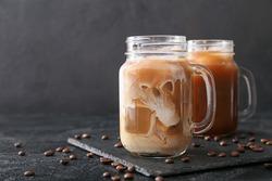 Mason jars of tasty iced coffee on dark background