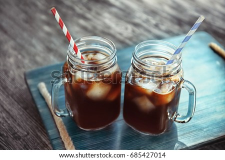 Mason jars with cold brew coffee on wooden tray #685427014