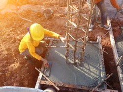Mason leveling and scrape concrete foundation with square trowel in a building construction site,Selective focus.