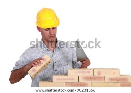 Mason making brick wall, studio shot