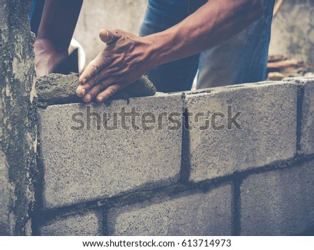 Mason or Brick builders are building walls in Thailand #613714973