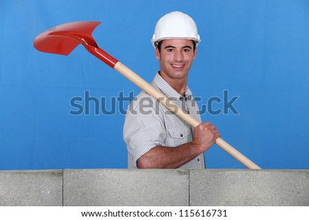 Mason with shovel building wall