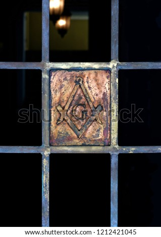 Masonic Symbol Detail on Iron Gate, Lights In The Background