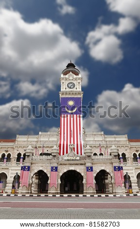 Masonry facade of the historical Sultan Abdul Samad Building in Merdeka Square, Kuala Lumpur, draped a giant Malaysian flag to celebrate Malaysian independence. The building is a tourist attraction.