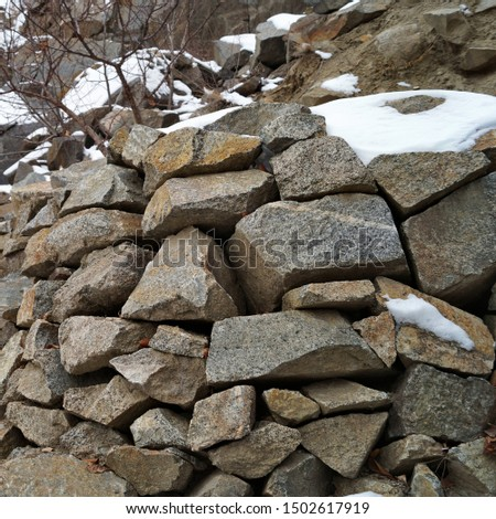 Masonry of rough rough stone sprinkled with snow
