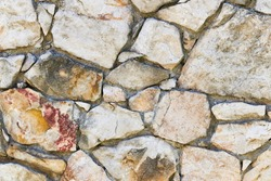 Masonry rock wall texture. Stones in foundation of old castle. Stone wall background for design or illustration