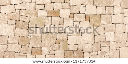 Masonry wall of stones with irregular pattern texture background