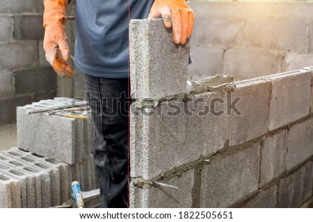 masonry worker make concrete wall by cement block and plaster at construction site ストックフォト ©