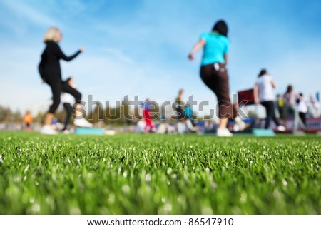 mass fitness at stadium at sunny autumn day, focus on green grass