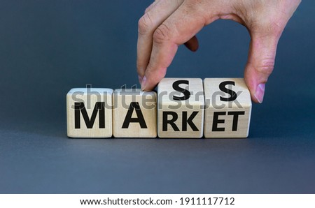 Mass market symbol. Businessman flips wooden cubes with words 'mass market'. Beautiful grey background, copy space. Business and mass market concept.
