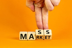 Mass market symbol. Businessman flips wooden cubes with words 'mass market'. Beautiful orange background, copy space. Business and mass market concept.