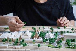 mass model of landscape design or garden design or landscape architecture in waterfront temple area with group of buildings and trees near community,   handmade work, bird's eye view, selective focus