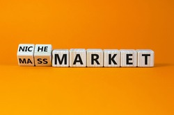 Mass or niche market symbol. Turned wooden cubes and changed words 'mass market' to 'niche market'. Beautiful orange background, copy space. Business and mass or niche market concept.