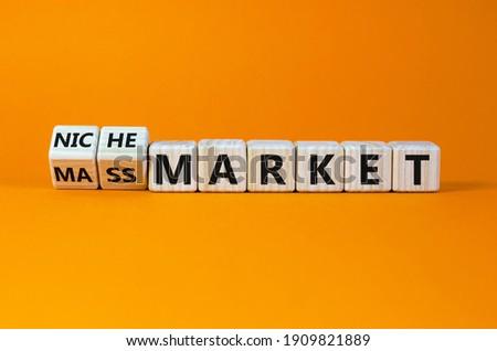 Mass or niche market symbol. Turned wooden cubes and changed words 'mass market' to 'niche market'. Beautiful orange background, copy space. Business and mass or niche market concept.