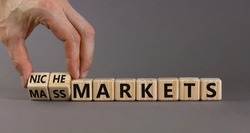 Mass or niche markets symbol. Businessman turns wooden cubes and changed words 'mass markets' to 'niche markets'. Beautiful grey background, copy space. Business and mass or niche markets concept.