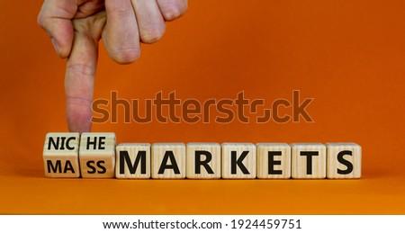 Mass or niche markets symbol. Businessman turns wooden cubes and changed words 'mass markets' to 'niche markets'. Beautiful orange background, copy space. Business and mass or niche markets concept.