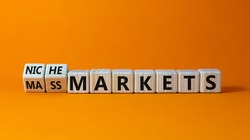 Mass or niche markets symbol. Turned wooden cubes and changed words 'mass markets' to 'niche markets'. Beautiful orange background, copy space. Business and mass or niche markets concept.