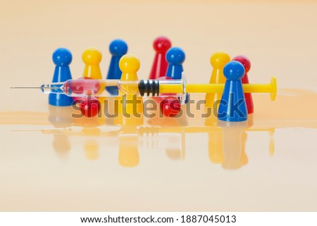 Mass vaccination of people against SARS-CoV-2 concept. Group of red, blue and yellow game pieces upright and syringe positioned on two red game pieces lying down on yellow background
