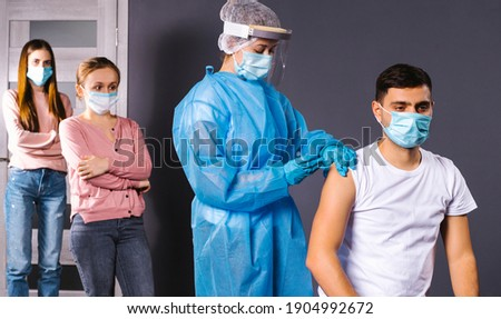 Mass vaccination of staff in the office. A nurse in protective gear puts a prick in a man's forearm.