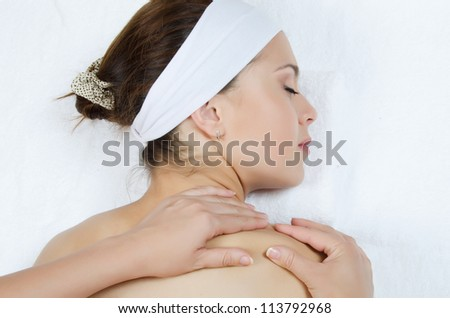 Massage a back at the young girl - stock photo