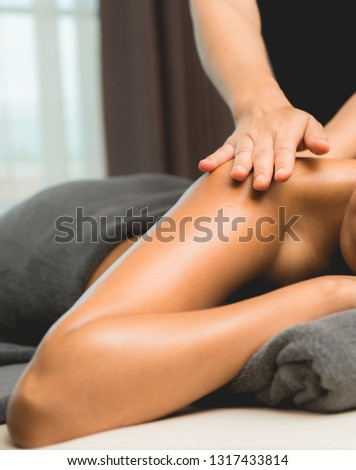 Massage and body care. Young woman tan or honey skin receiving  relaxing shoulders massaging in a spa house. Beautiful woman having massage in the spa salon for beauty care.