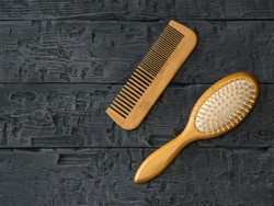 Massage comb and comb comb on a wooden table. Device for combing hair.