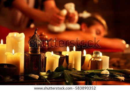 Massage of woman in spa salon. Girl in massaging spa salon. Luxary interior in oriental therapy salon. Close up of female massage hands give herbs hot ball therapy. Burning candles on foreground.