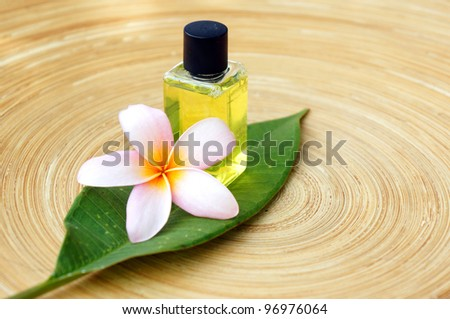 Massage oil for tropical spa concept with plumeria flowers on wooden plate - stock photo