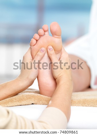 Massage on the foot in spa salon, close-up shot - colored background