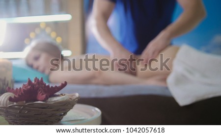 Massage parlor - young girl gets relaxing healing therapy, de-focused #1042057618