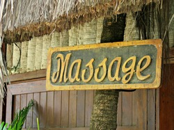 Massage sign in front of a wooden hut in a tropical setting
