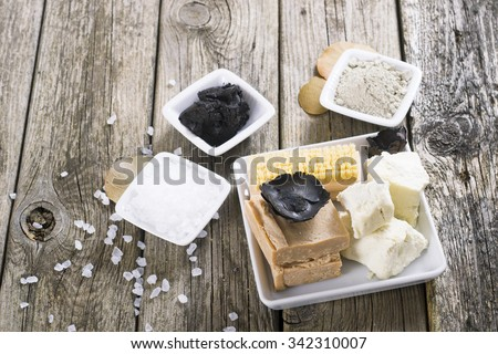 massage spa setting: cosmetic clay, mud, shea butter, organic soaps, bath salt, brush on old wood table background