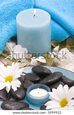 Massage stones, candle and daisies - stock photo