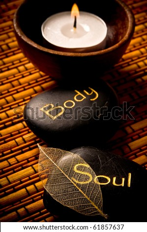 massage stones - relax, body, soul - and a candle over bamboo background like a concept for wellness, reiki and yoga symbols