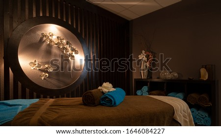 Massage table with colorful towels on a wooden background with faint lights to relax Foto stock ©