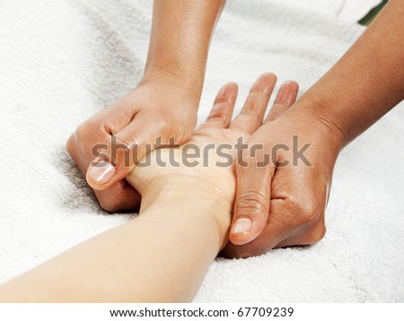 massage therapist gently kneading female hand