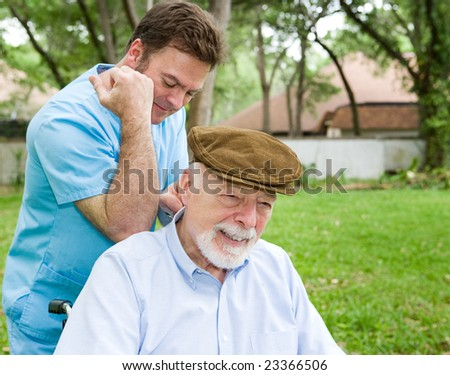 Massage therapist massaging a senior man's back in a beautiful outdoor setting.