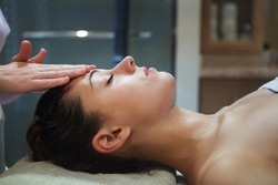 Masseur doing facial massage of an adult woman in the spa salon