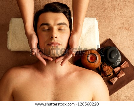 Masseur doing head massage on man in the spa salon