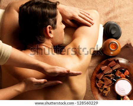 Masseur doing massage on man body in the spa salon Beauty treatment concept