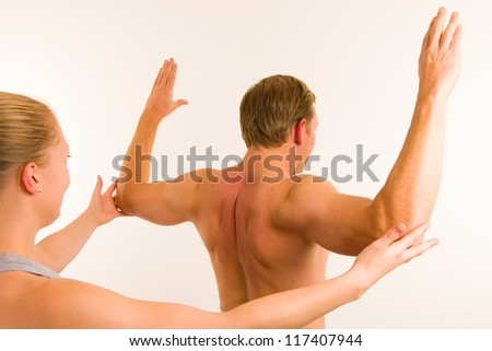 Masseur examining body of men, white wall on background