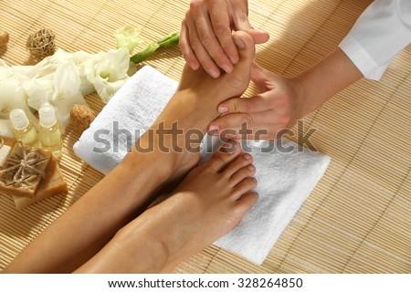 Masseur making feet massage in spa salon