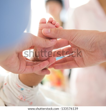 Masseur massaging little baby's foot.
