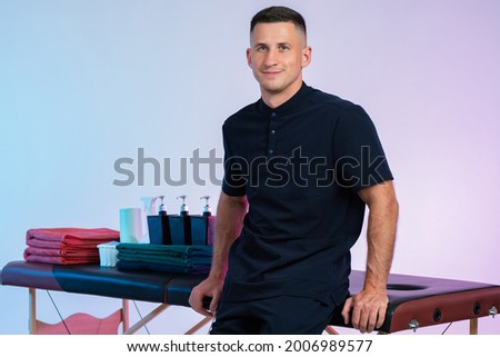 Masseur next to the couch. Male masseur posing. The guy is working as a masseur. Massage room employee. SPA center worker. Career in the spa business. Massage supplies in the background Stockfoto ©