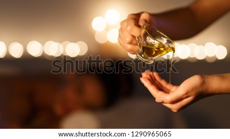 Masseur pouring massage oil, woman lying on background at spa center ストックフォト ©