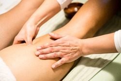 Masseuse woman hands giving a leg massage, finding a contracture, trigger point, a tight part in the muscle