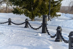 Massive cast iron chains dangling between pillars against a backdrop of white snow. Close-up. Photo taken on a sunny winter day in Siberia (Russia)