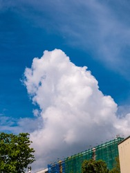 Massive cloud - towering cumulus - forming over building under construction with scaffolds and safety net