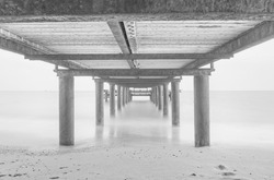 Massive concrete pier leading to horizon surrounded by Mediterranean sea. Long exposure shot made in Belek, Turkey. August 2020. Black and white picture